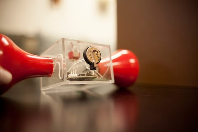 To demonstrate the supercapacitor's ability to store power, the researchers modified an off-the-shelf hand-crank flashlight (the red parts at each side) by cutting it in half and installing a small supercapacitor in the center, in a conventional button battery case, seen at top. When the crank is turned to provide power to the flashlight, the light continues to glow long after the cranking stops, thanks to the stored energy. Photo: Melanie Gonick