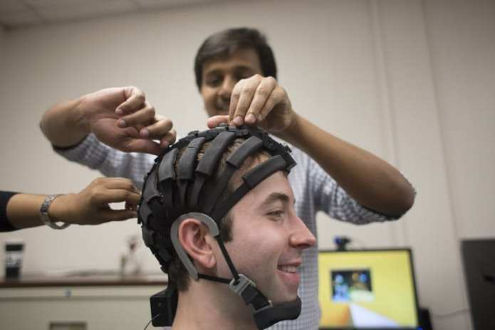 Nikhil Dusane, a graduate student in information science and technology, puts one of the business and information technology department's EEG headsets on Samuel Smith, a senior in information science and technology, in the university's Laboratory for Information Technology and Evaluation.