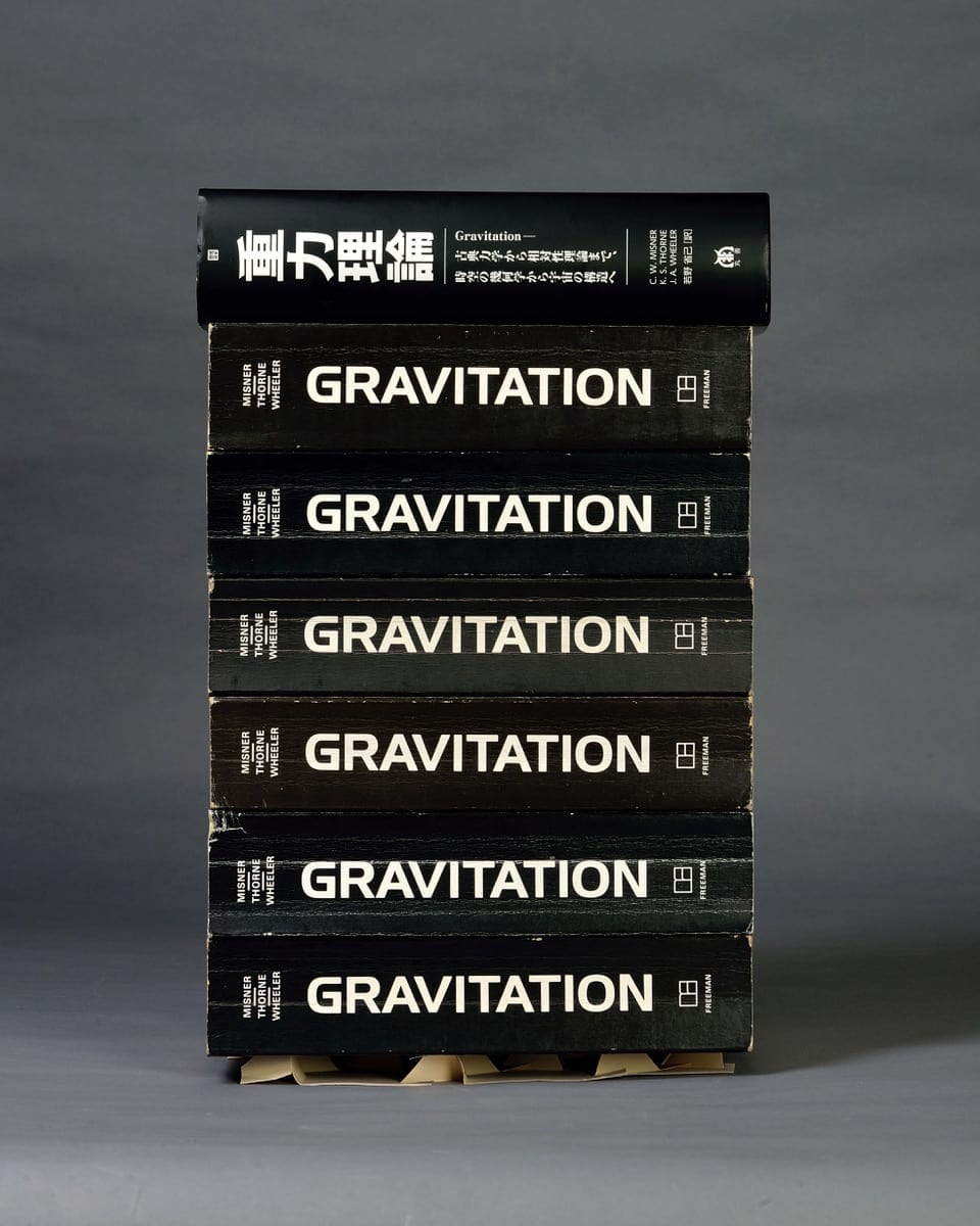 """Wang and the Kamien lab collected the largest books they could find from across the physics department. They found that seven copies of the five-pound """"Gravitation"""" textbook could be supported by a single kirigami sheet. (Image: Randall Kamien)"""