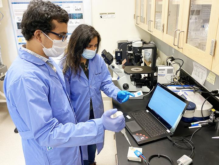 Med School Research Scientist Timsy Uppal and Engineering post-doctoral researcher Bhaskar Vadlamani testing the SARS-CoV-2 nanosensor.