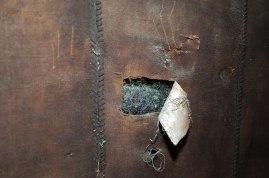 Particolare dello sotto-finestrino in cuoio scamosciato con strappo che rende visibile il crine animale utilizzato per l'imbottitura e la tela di lino per la messa in bianco.