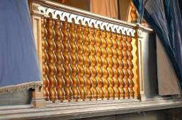 Colonnine tortili in ghisa dorate usate sia nella balaustra che come supporto di sostegno per il tetto.