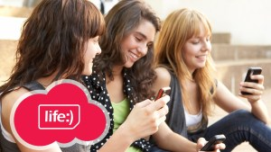 Photo of three young women looking at their smartphones, Life Ukraine Logo on the foreground