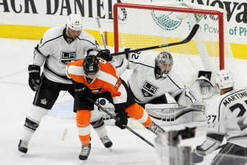 Defenseman Robyn Regehr (#44) of the Los Angeles Kings shoves Left Wing Michael Raffl (#12) of the Philadelphia Flyers with one hand while teammate Goalie Jonathan Quick (#32) tries to keep his eye on the puck
