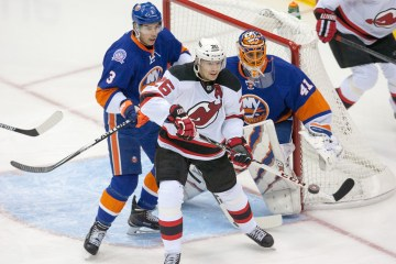 New York Islanders defenseman Travis Hamonic #3 moves New Jersey Devils left wing Patrik Elias #26 away from New York Islanders goalie Jaroslav Halak #41 as he deflects a shot Saturday Night at the Nassau Veteran Memorial Coliseum. Final score Islanders 3 Devils 1
