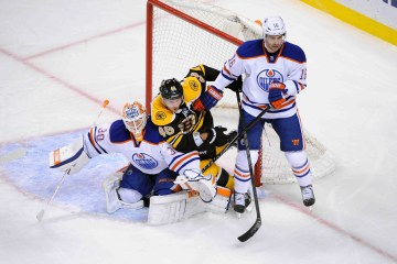 Boston Bruins center David Krejci (46) caught between Edmonton Oilers right wing Teddy Purcell (16) and  goalie Ben Scrivens (30)