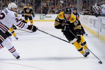 Boston Bruins left wing Brad Marchand (63) moves the puck past Chicago Blackhawks defenseman Michal Rozsival (32)