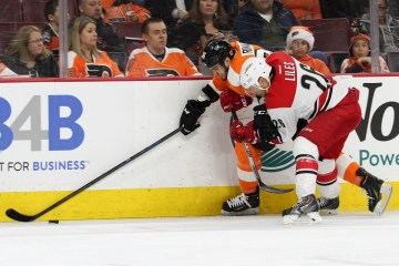 Defenseman John-Michael Liles (#26) of the Carolina Hurricanes defends against Right Wing Zac Rinaldo (#36) of the Philadelphia Flyers