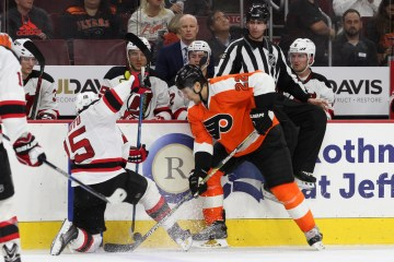 Left Wing Tuomo Ruutu (#15) of the New Jersey Devils and Defenseman Luke Schenn (#22) of the Philadelphia Flyers battle for the puck along the boards during the third period