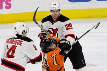 Defenseman Shayne Gostisbehere (#53) of the Philadelphia Flyers takes a stick from Defenseman Damon Severson (#28) of the New Jersey Devils during the this period