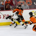 Left Wing Conor Sheary (#43) of the Pittsburgh Penguins splits between Defenseman Nick Schultz (#55) and Center Scott Laughton (#21) of the Philadelphia Flyers during the first period