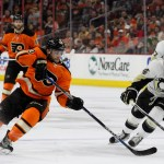 Defenseman Shayne Gostisbehere (#53) of the Philadelphia Flyers passes the puck against Left Wing Chris Kunitz (#14) of the Pittsburgh Penguins during the third period