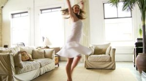 stock-footage-woman-dancing-in-living-room-with-sunflowers[1]