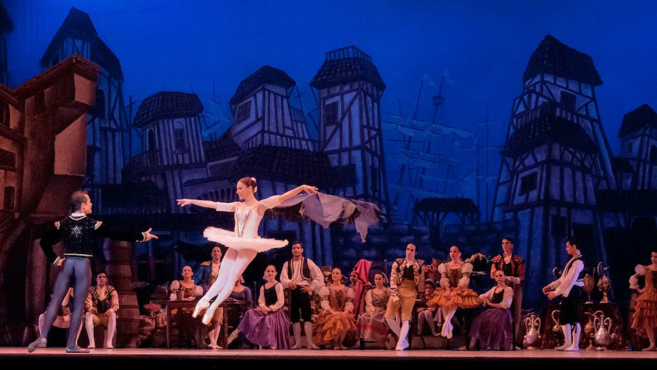 Ballerina leaps into male ballet dancer's arms in front of large company onstage during a performance.