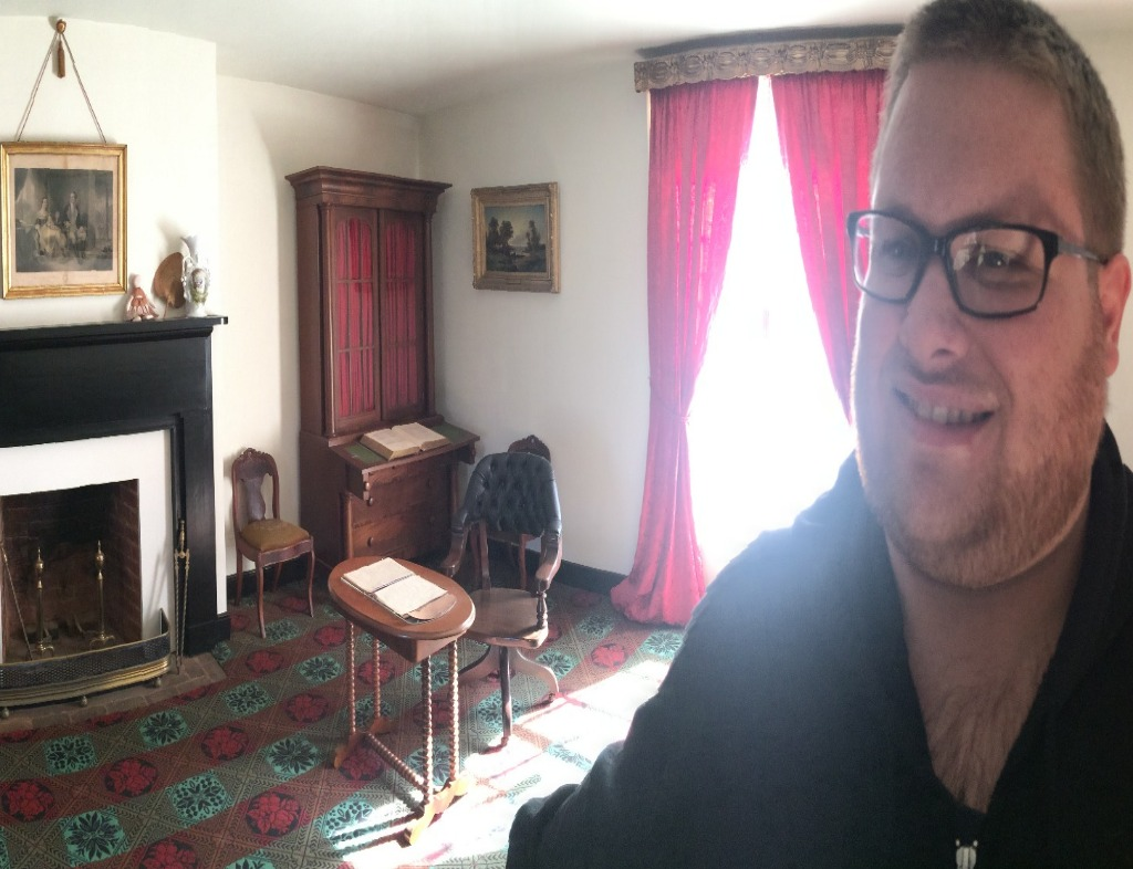 Douglas wearing a black sweatshirt standing in front and to the right of the chair where Ulysses S. Grant sat during the Surrender at Appomattox. There are red drapes behind the chair with sunlight coming through.