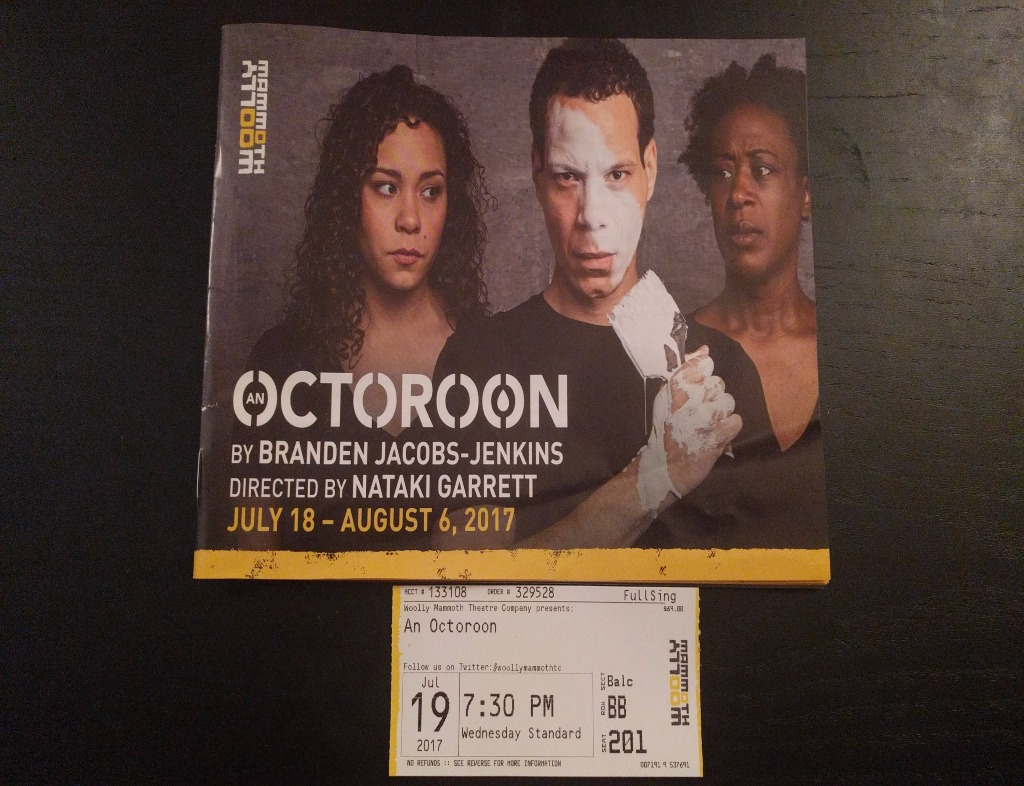"""The cover of the program for """"An Octoroon"""" by Branden Jacobs-Jenkins. Two African American women on either side of an African American man who has a paint brush in his hand with white paint on it, which has just put a streak down his face. The ticket for the performance is below the program."""