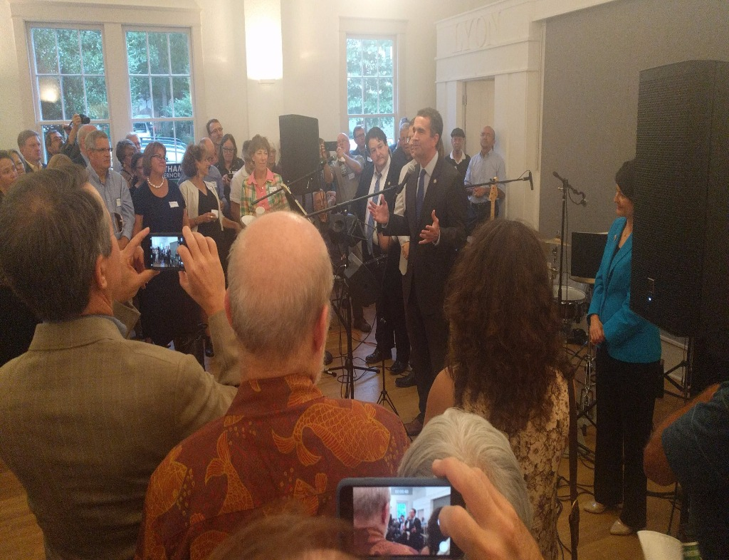 A view from the front of a room of a Ralph Northam for Virginia Governor fundraising event. Lt. Gov. Northam speaks with hands apart. He wears a suit and is facing the left. Surrounding him are other elected officials in business attire and attendees form a horse-shoe that faces right.