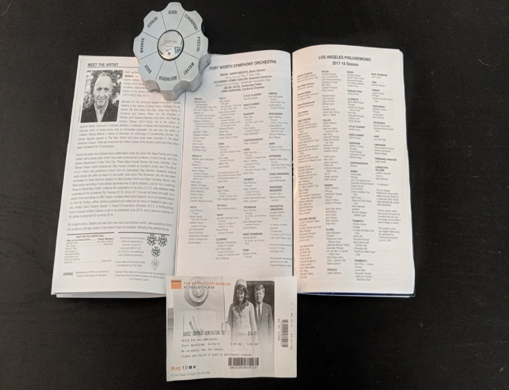 Three Programs in black and white (L-R: David Sedaris, Fort Worth Symphony Orchestra, Los Angeles Philharmonic) and an admission ticket for the Sixth Floor Museum below the middle program on top of a black wooden table. There is a silver octagonal paperweight between the left two programs.