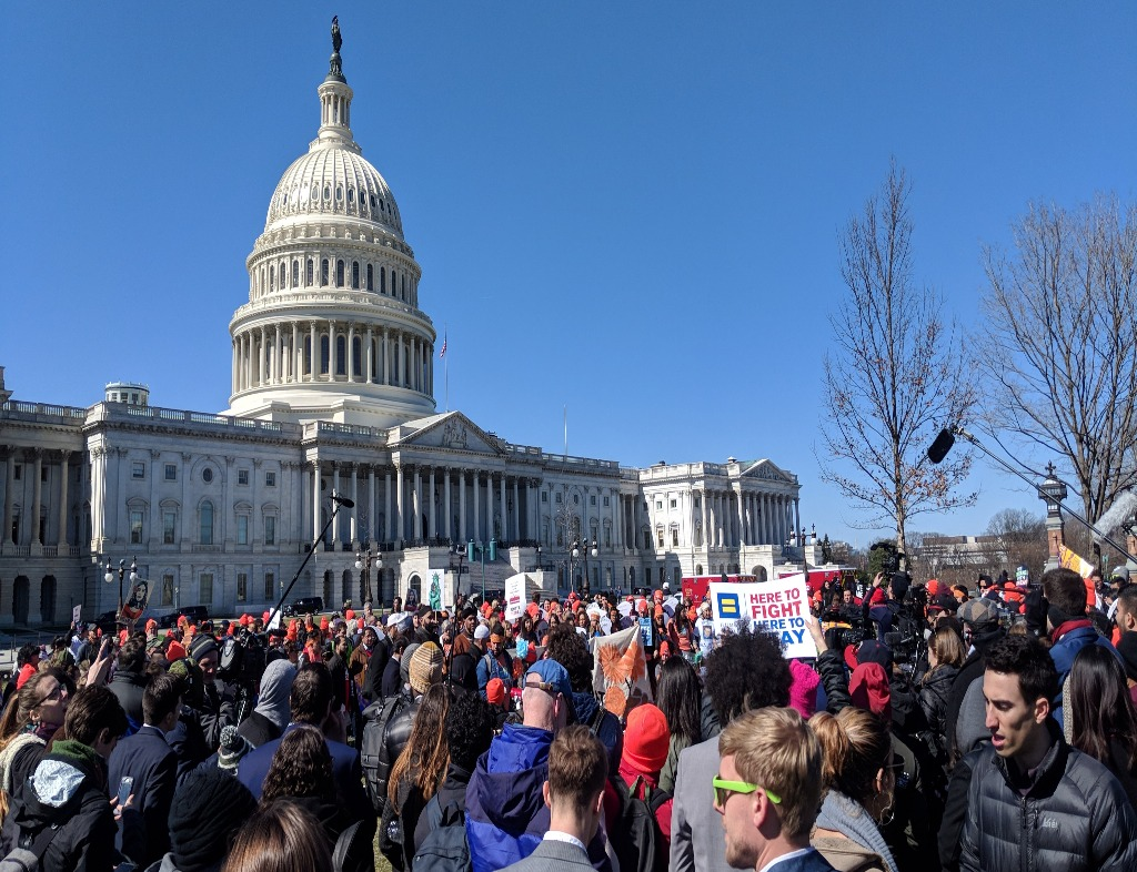 Protestors in front of the east side of the US Capitol Building. The Dome is to the left of the photo, and there is a boom mic on the right side in front of a leaveless tree. The sky is completely blue.