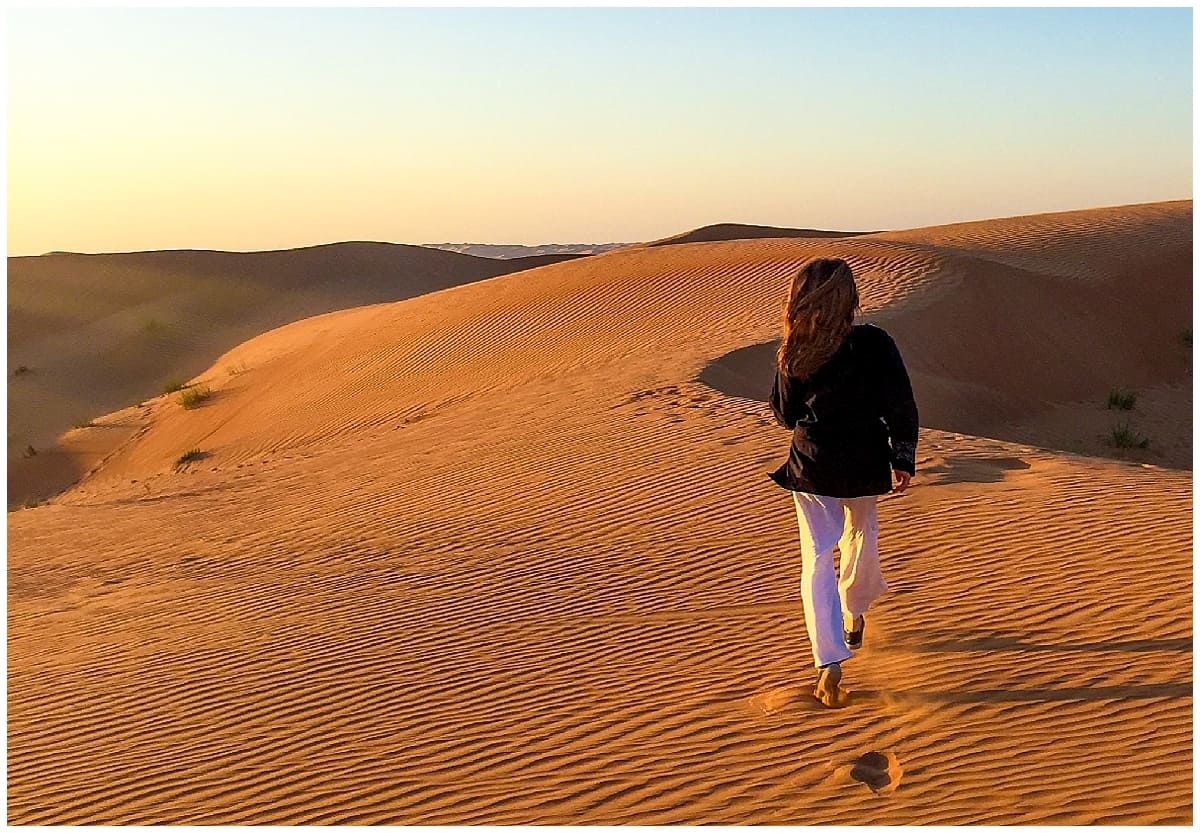 Abi from Inside the Travel Lab striding into the desert