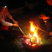 Menschen beim Stockgrillen am offenen Feuer
