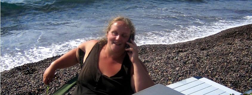 Lara telefoniert am Strand