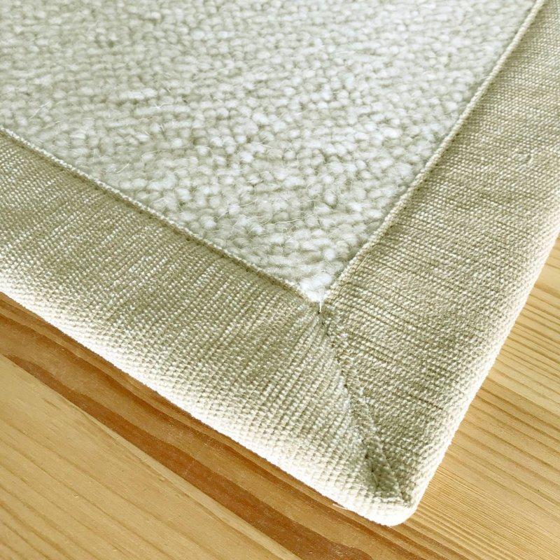 tapis sur mesure ecru en laine bouclee finition gansee beige