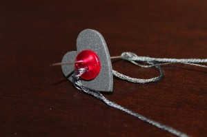 black foam heart attached to red button with gray embroidery floss