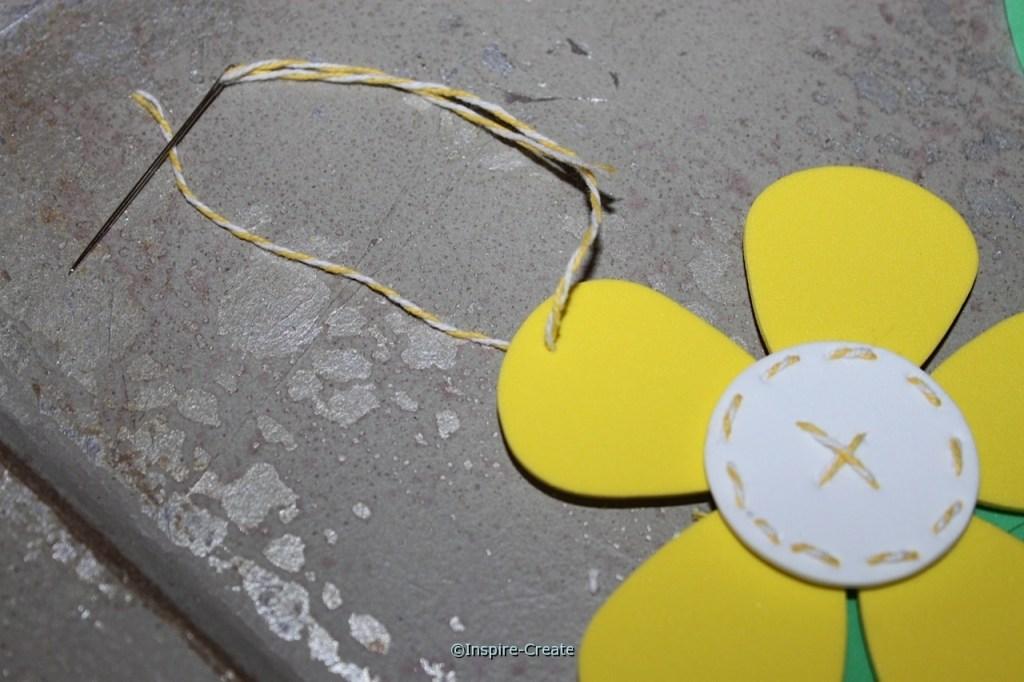 add baker's twine to hang flower