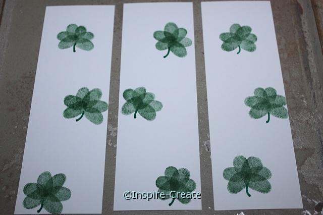 Add stems to fingerprint shamrocks with a marker.