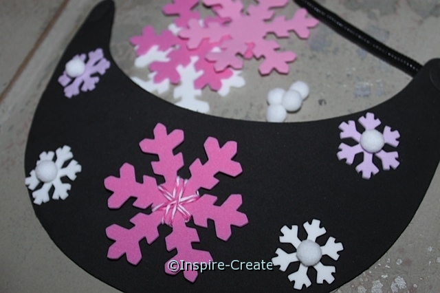 Attach foam snowflakes to foam visor with glue dots.