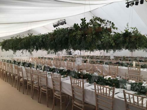 Framed tent with flat ivory linings, long tables, chivari chairs, and horizontal ladders suspended above the tables decorated with foliage and hanging glass tea light baubles