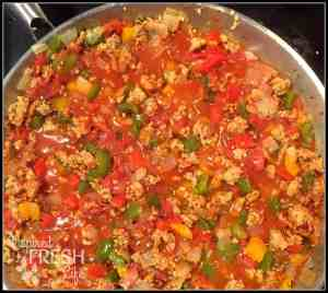 sausage, peppers, onion, and tomatoes cooking in a skillet