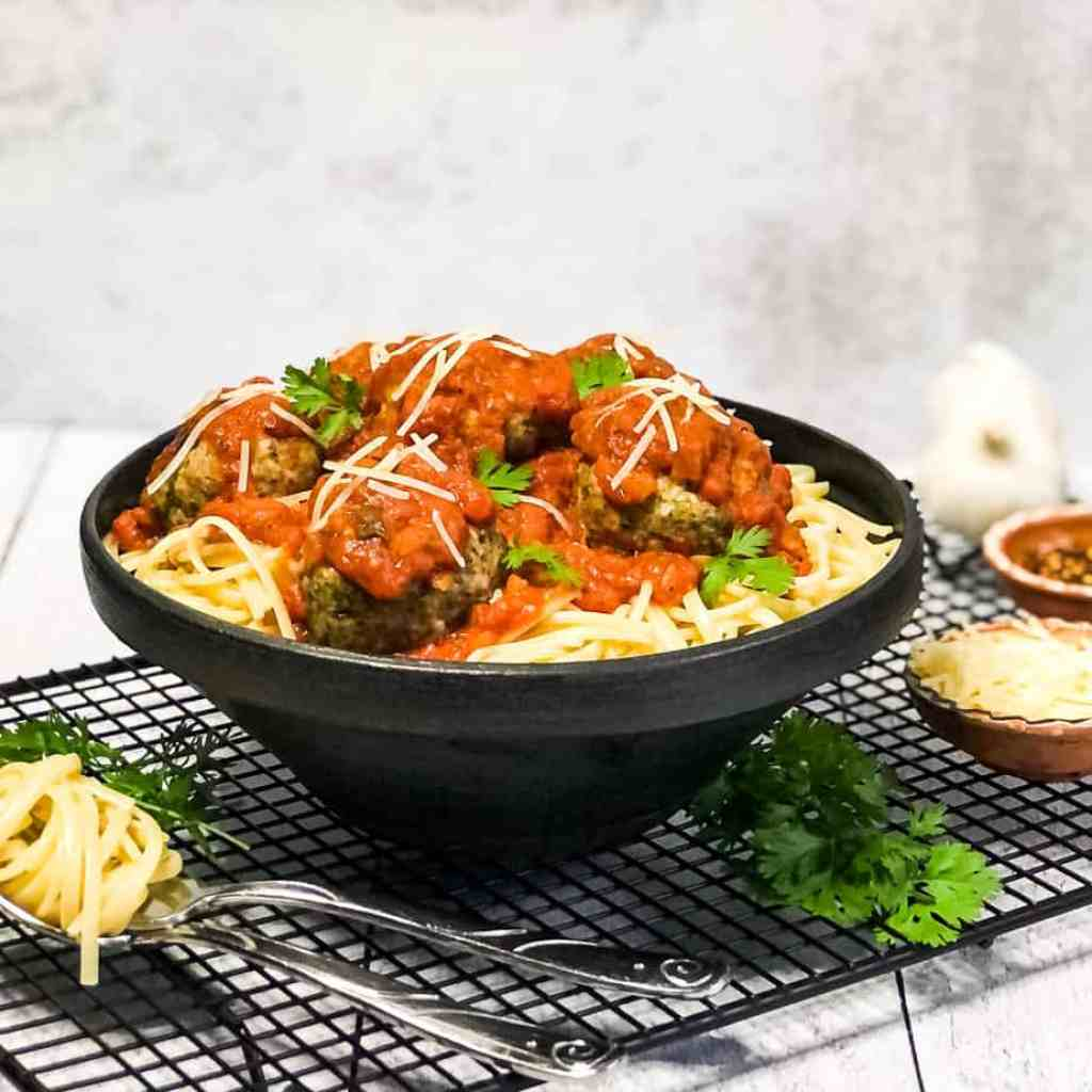 Black bowl holding pasta, Italian Meatballs, and marinara in a black bowl with ingredients blurred in background.