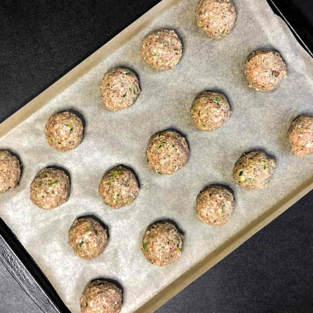 Raw meatballs on a sheet pan lined with parchment paper.