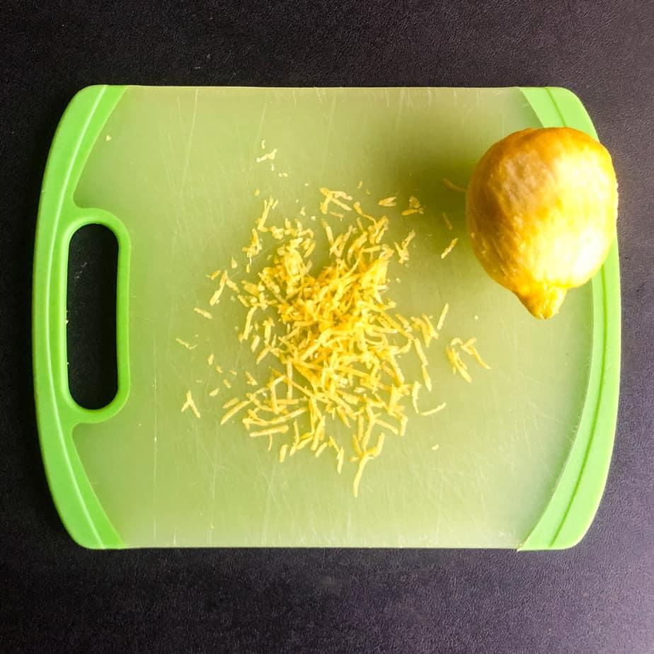 Whole lemon and lemon zest on a green cutting board.