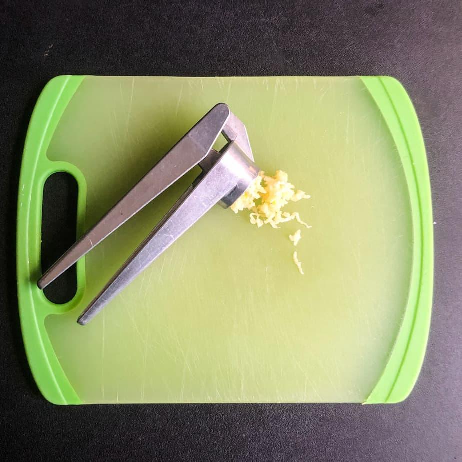 Garlic press and minced garlic on a green cutting board.