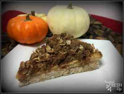 Snickerdoodle Apple Crisp on a white plate with mini pumpkins in the background