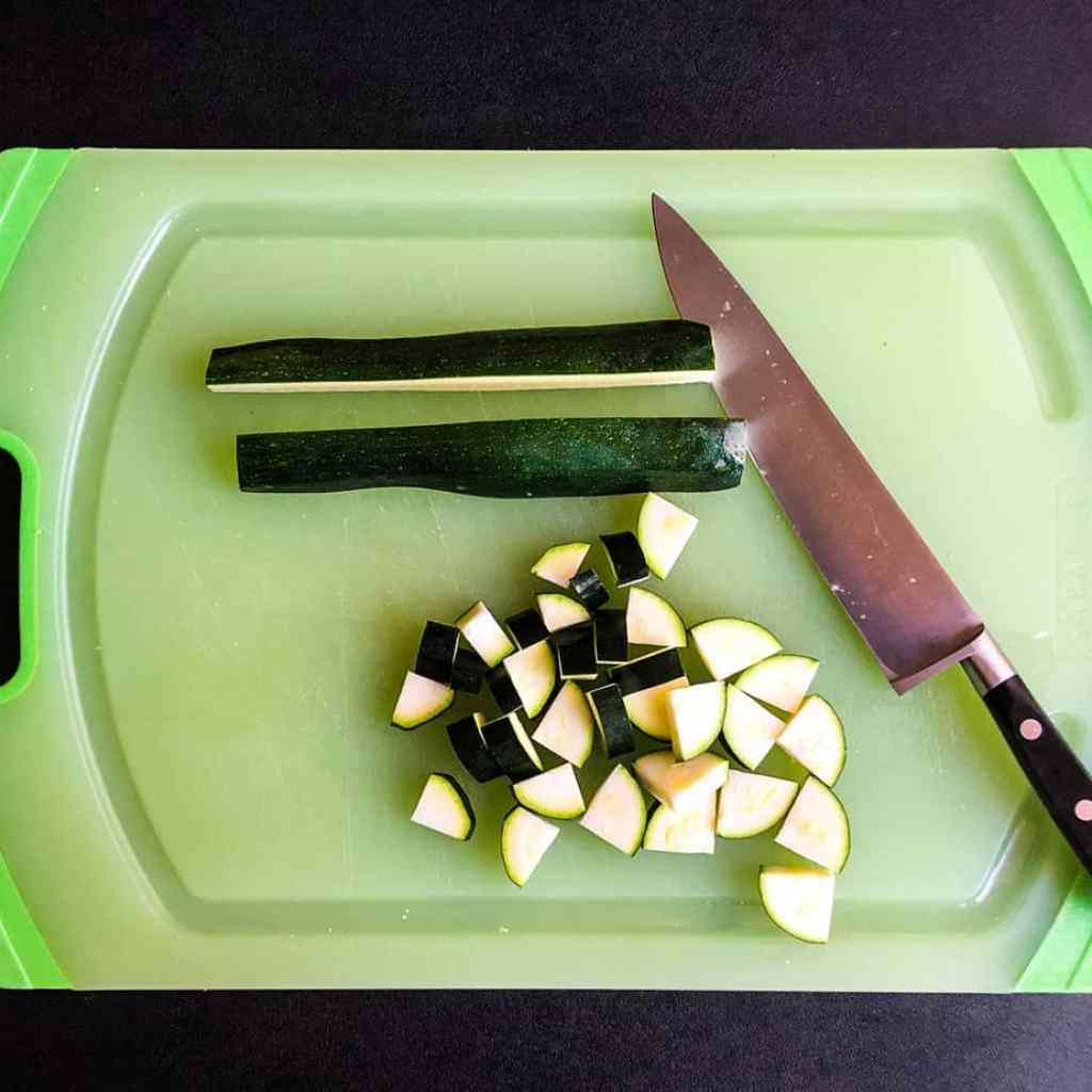 Zucchini being chopped on a green cutting board.