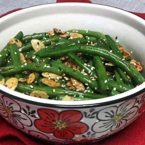 Toasted Sesame Green Beans garnished with sesame seeds in a serving bowl, close up view