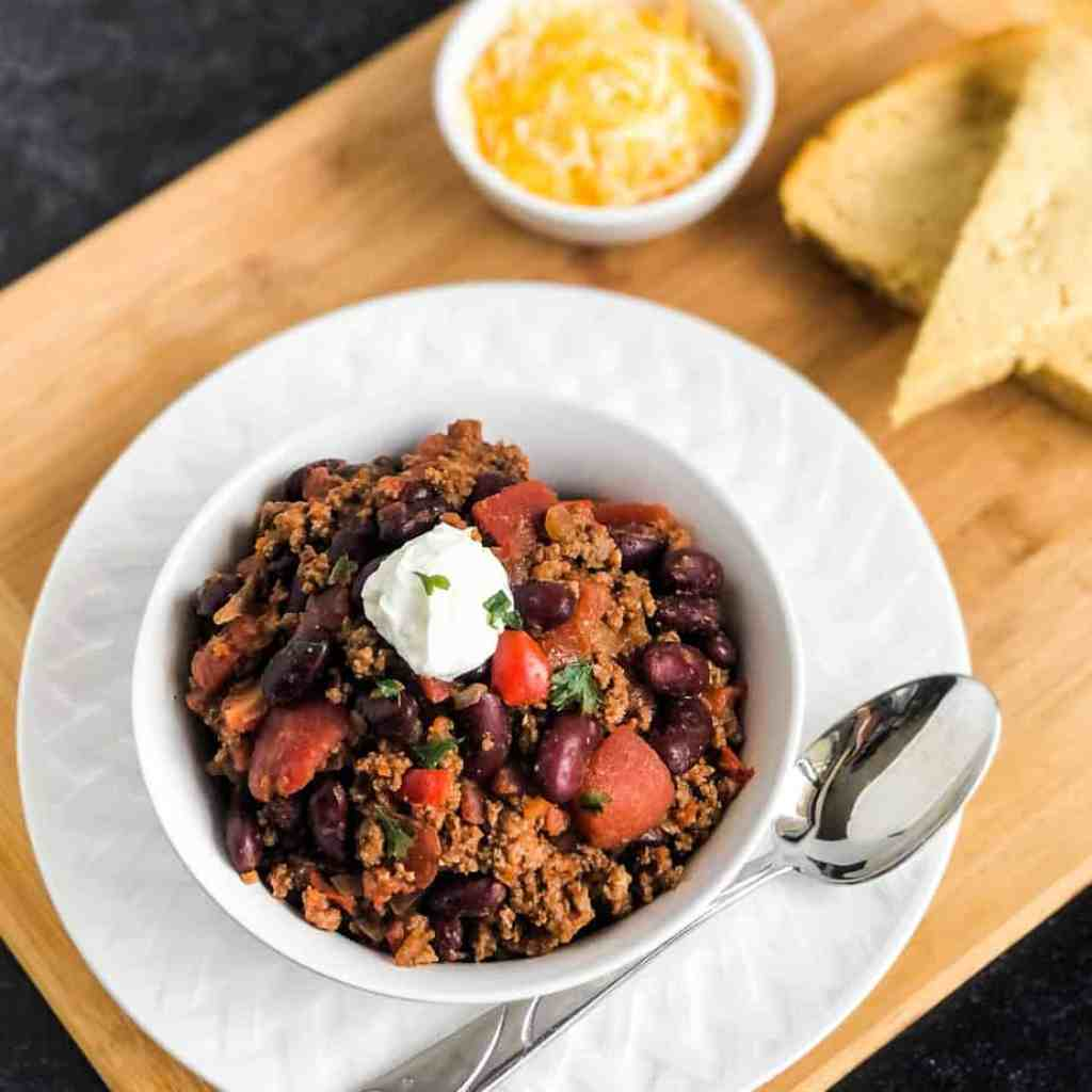 Overhead shot of Slow Cooked Chili in a white bowl garnished with sour cream and cilantro.