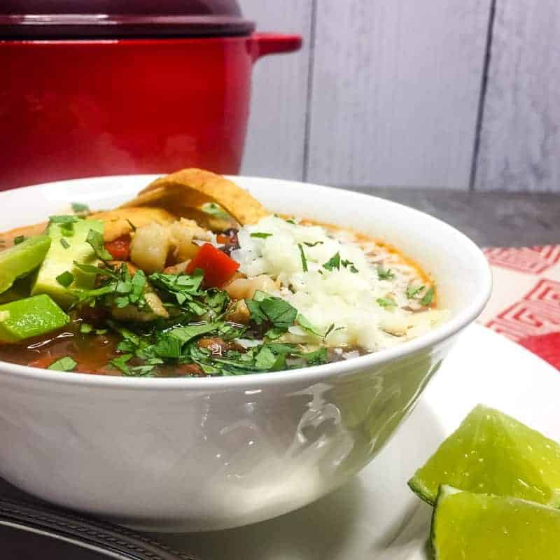 Vegetarian Tortilla Soup in a white bowl garnished with cheese, tortilla strips, avocado, cilantro, and lime.