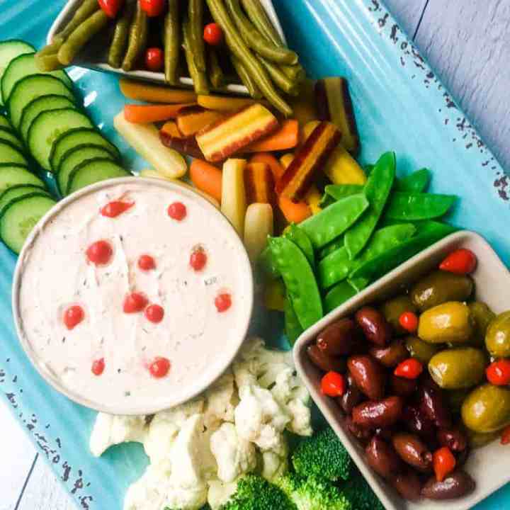 Overhead shot of Everything but the Bagel Veggie Dip on a blue platter with assorted vegetables, olives, and pickled green beans.