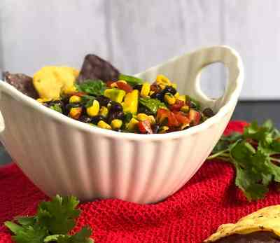 Side view of Cowboy Caviar in a white bowl on a red cloth.