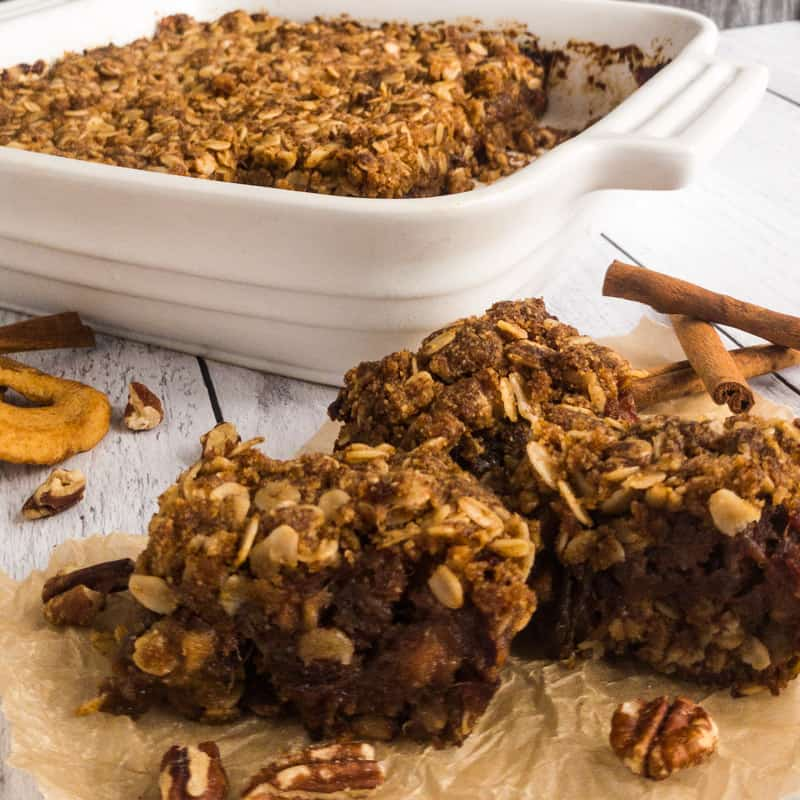 Cut Apple Date Bars on unbleached parchment in front of the white baking dish with loose nuts and cinnamon stick garnish.
