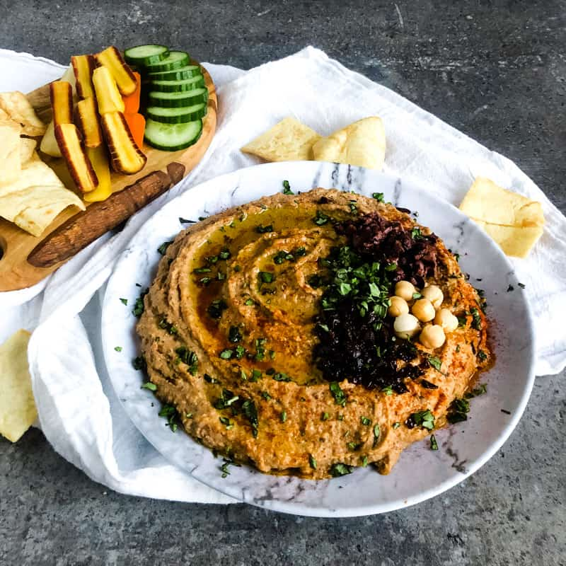 Close of Mediterranean Hummus on a faux marble plate with vegetable slices and pita chips in the background.