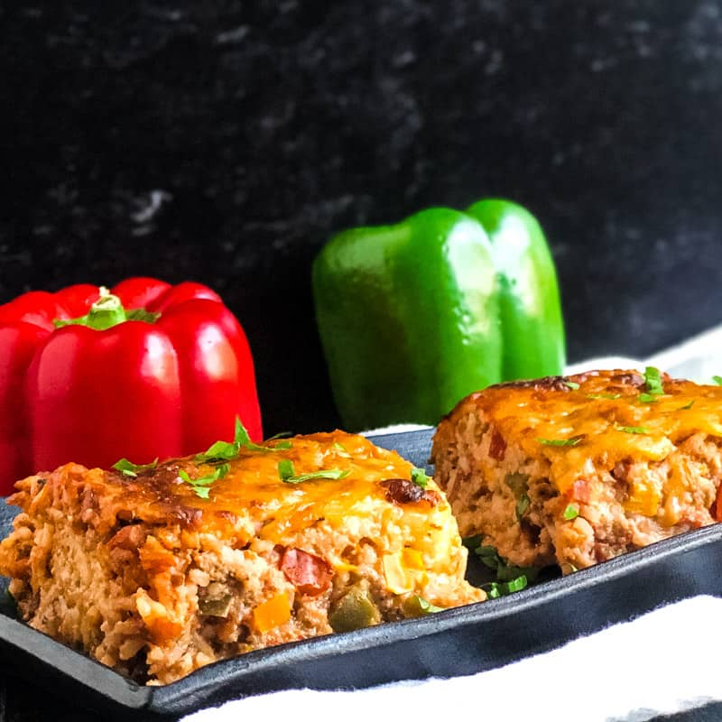 Close up of Unstuffed Pepper Casserole with red and green peppers in the background.