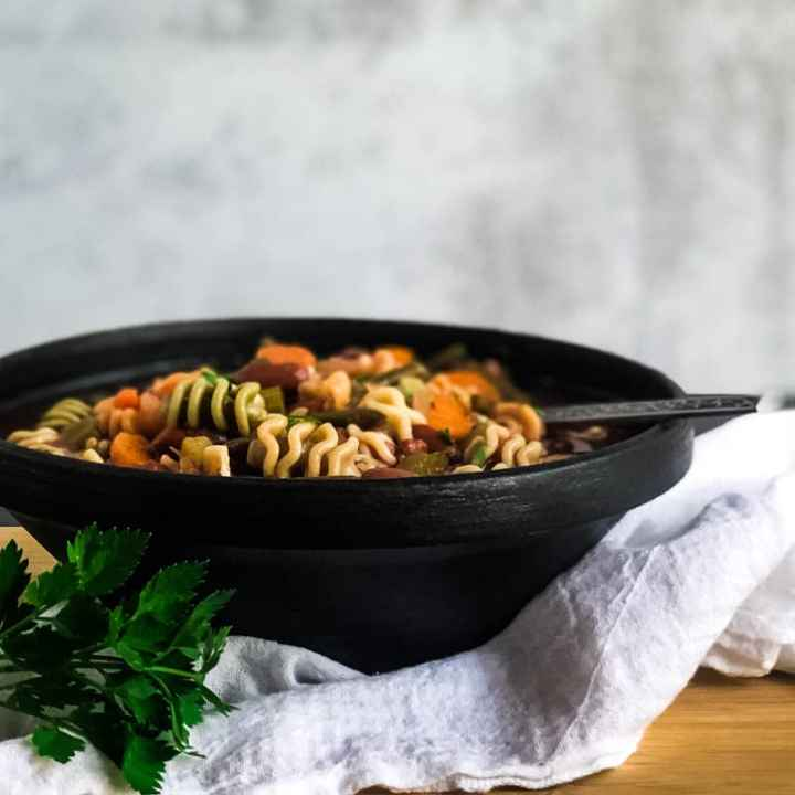 Close up of Vegetable Minestrone in a black bowl garnished with fresh parsley.