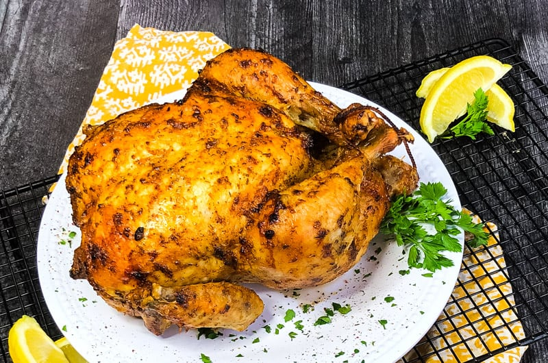 Air Fryer Whole Chicken on a white plate over a gold patterned kitchen towel with parsley and lemon garnish.