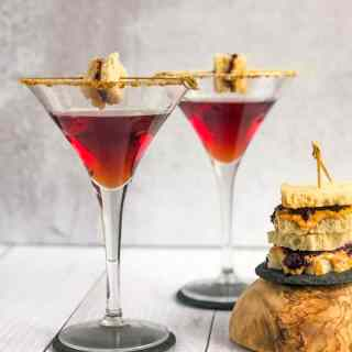 Peanut Butter and Jelly Martini with a small stack of peanut butter and jelly sandwiches to the side.